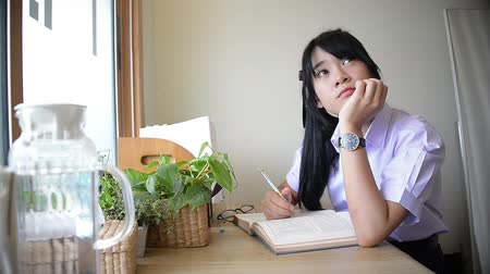 Cute Asian Thai high school girl in uniform studying and thinking on desk with little moment of imagination distraction or daydream in private room in schoolgirl fashion and education concept HD Dostupné videozáznamy