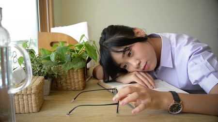 Cute Asian Thai high school girl in uniform lie on text book playing with her glasses with boredom on desk in her room with plants and window decoration in lazy schoolgirl fashion and education concept HD