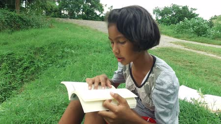 Poor Asian Thai girl is reading and studying alone in casual clothes in green field rural nature environment. Kindergarten or elementary schoolgirls learning in kid education concept in 4k