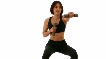 Pretty Thai Asian sportswoman is doing dumbbell punch in both hands posture. Weight exercise cardio workout in white isolated background in fitness concept Dostupné videozáznamy