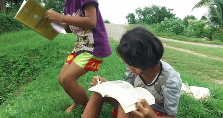 Poor Asian Thai girl is reading and studying alone in casual clothes in green field rural nature environment and then her friend join in with. Kindergarten or elementary schoolgirls learning education concept in 4k