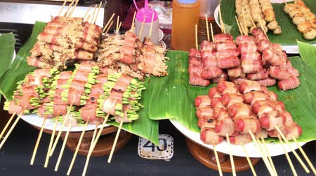 Slow motion of skewer pork sausage and ham barbecue in native open market of Thailand. Charcoal grill meat sausage and ham roll with vegetable and golden needle mushroom on a stick native Thai cuisine food with camera movement in 4k.