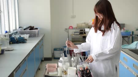 Closeup of Asian Thai girl scientist or science college student in labcoat is observing flask bottles for germ growth rate testing with happy expression in biology research laboratory. Dostupné videozáznamy
