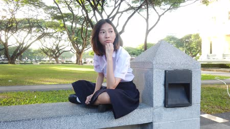 frustração : Cute Asian Thai high schoolgirl in uniform sits on stone bench of the park in bad mood, angry or concern about something or someone in school dramatic concept 4k