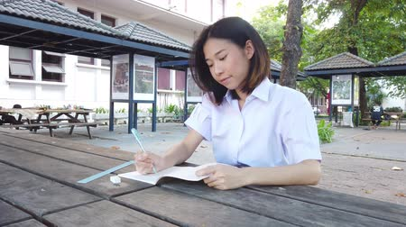 Cute Asian Thai high schoolgirl in uniform having fun with homework while writing with smiley face on outdoor bench in school education concept 4k