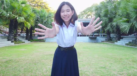 torcendo : Cute Asian Thai high schoolgirl student in school uniform waves her hand in front of the camera with playful fun expression to cheer you up in green garden environment 4k