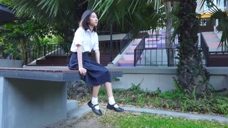 Cute Asian Thai high schoolgirl in uniform sits on the edge of building and swings her feet chilling with day dream on outdoor bench in school education concept 4k