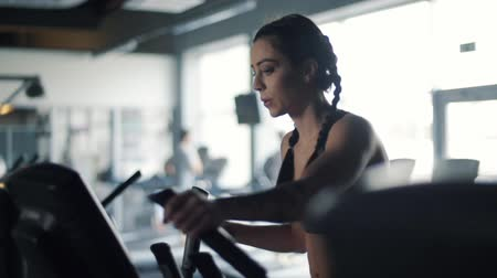 elliptical : Young woman using elliptical machine in gym