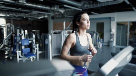 elliptical : Thirsty woman running on treadmills Stock Footage