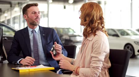 persuasion : Salesman giving customer a contract and keys Stock Footage