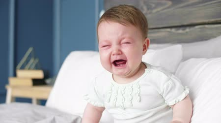 colic : Crying baby sitting on bed Stock Footage
