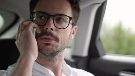 vehicle part : Passenger talking by mobile phone in a taxi Stock Footage