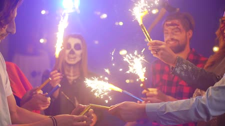 friendship dance : Friends having fun with sparkler at halloween party Stock Footage