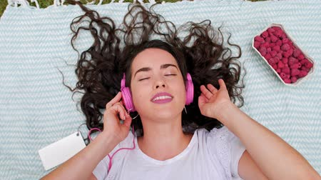 şan : Girl listening to music through headphones at the park
