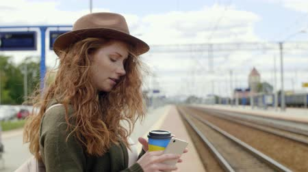 прибытие : Girl with coffee and mobile phone waiting for the train