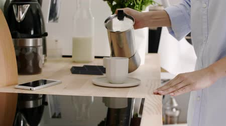 induction cooker : Woman pouring herself a mug of black coffee in kitchen