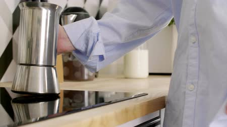 induction cooker : Part of woman making coffee in her kitchen Stock Footage