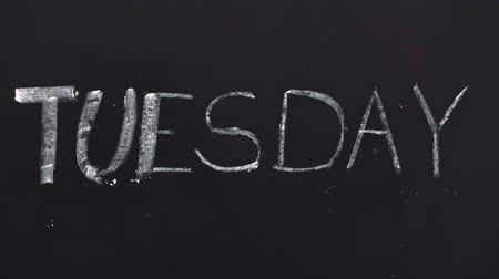 beginnings : Word tuesday written on the blackboard Stock Footage