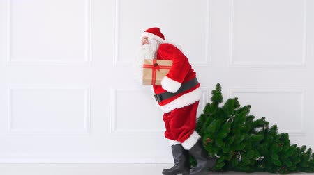 overweight : Tired santa claus with christmas tree and christmas present