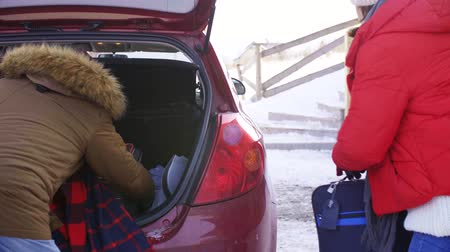 unload : Mature couple unpacking a car trunk