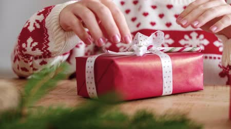 wrapped up : Close up of girls hands decorating the christmas present Stock Footage