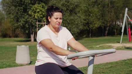 baixo teor de gordura : Woman using exercise bike in public park