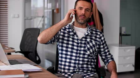 deficientes : Man talking by mobile phone in office