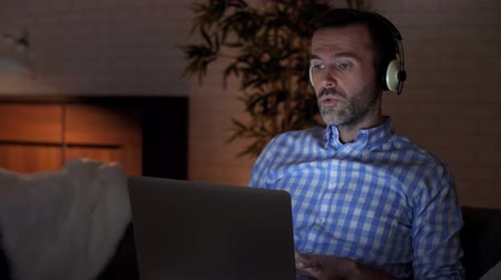 ouvir : Man using laptop and listening to music in home office