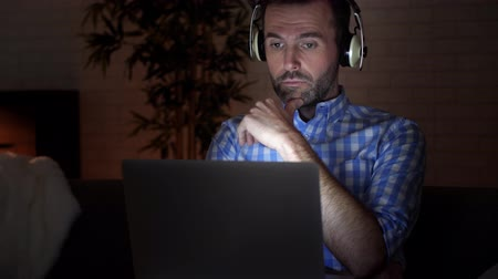 use laptop : Focused man using laptop at night Stock Footage