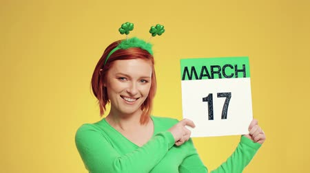 pasu nahoru : Woman showing calendar with a date for Saint Patricks Day Dostupné videozáznamy
