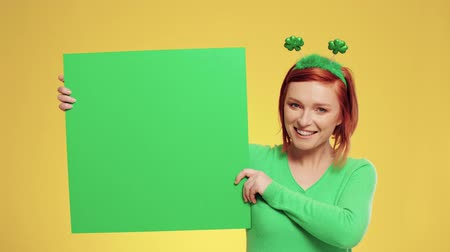 poszter : Smiling woman with green banner in studio shot