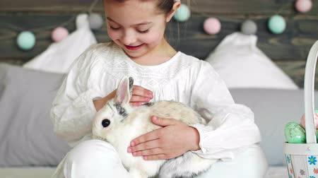 кролик : Girl sitting next to easter basket and stroking the rabbit