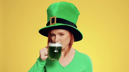 тост : Woman with leprechauns hat drinking beer in the studio shot