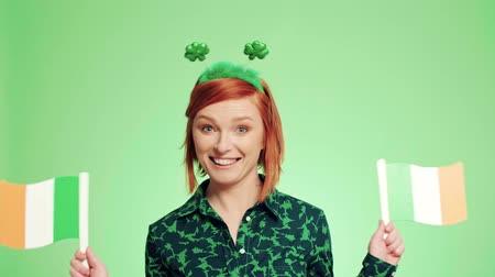 a smile : Portrait of playful woman waving Irish flags Stock Footage