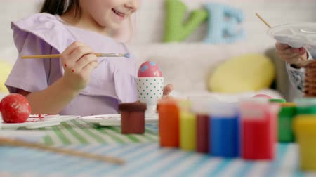 easter : Happy girl painting easter eggs Stock Footage