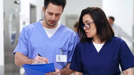 cirurgia : Two doctors discussing some medical records in the corridor