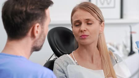 зубная боль : Young woman with toothache talking to dentist in dentists clinic,
