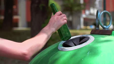 elválasztás : Mans hand throwing away, glass bottle in recycling bin Stock mozgókép