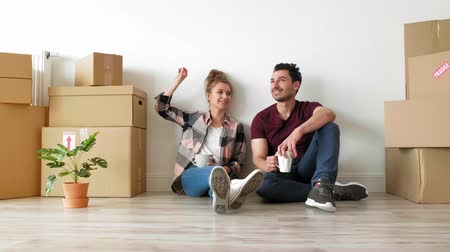 異性のカップル : Young couple taking a break while moving house 動画素材