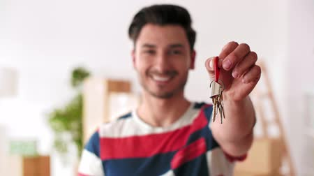 Young man holding a key ring to his new house