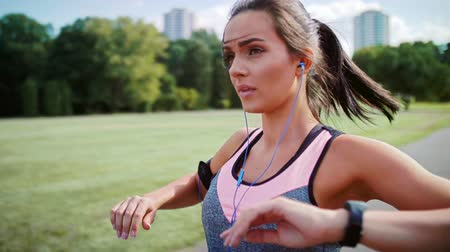 Young woman listening to music and warming up before running Vídeos