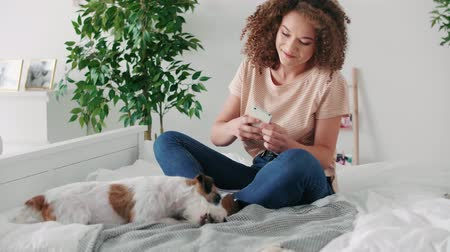 solo adultos : Teenage girl photographing her dog in the bedroom