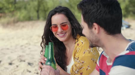 sieves : Young couple drinking cold beer on the beach
