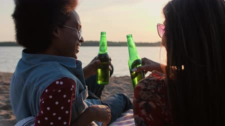 Couple drinking beer and watching the sunset on the beach