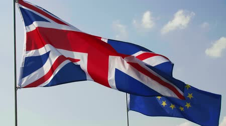 ayrılmak : British Flag and European Union flag on blue sky Stok Video