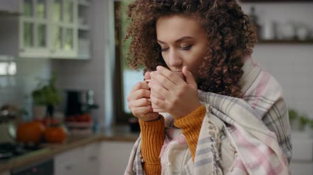 home life : Worried woman wrapped in a blanket drinking hot tea