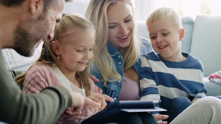 sieves : Happy family using a tablet in living room Stock Footage