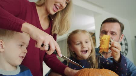 halloween pompoen : Handheld video shows of family drilling pumpkins for Halloween