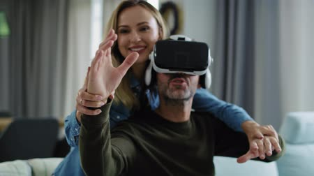 Modern couple using virtual reality simulator in living room Filmati Stock