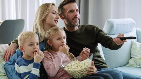 watch tv : Family with two children watching tv in living room Stock Footage